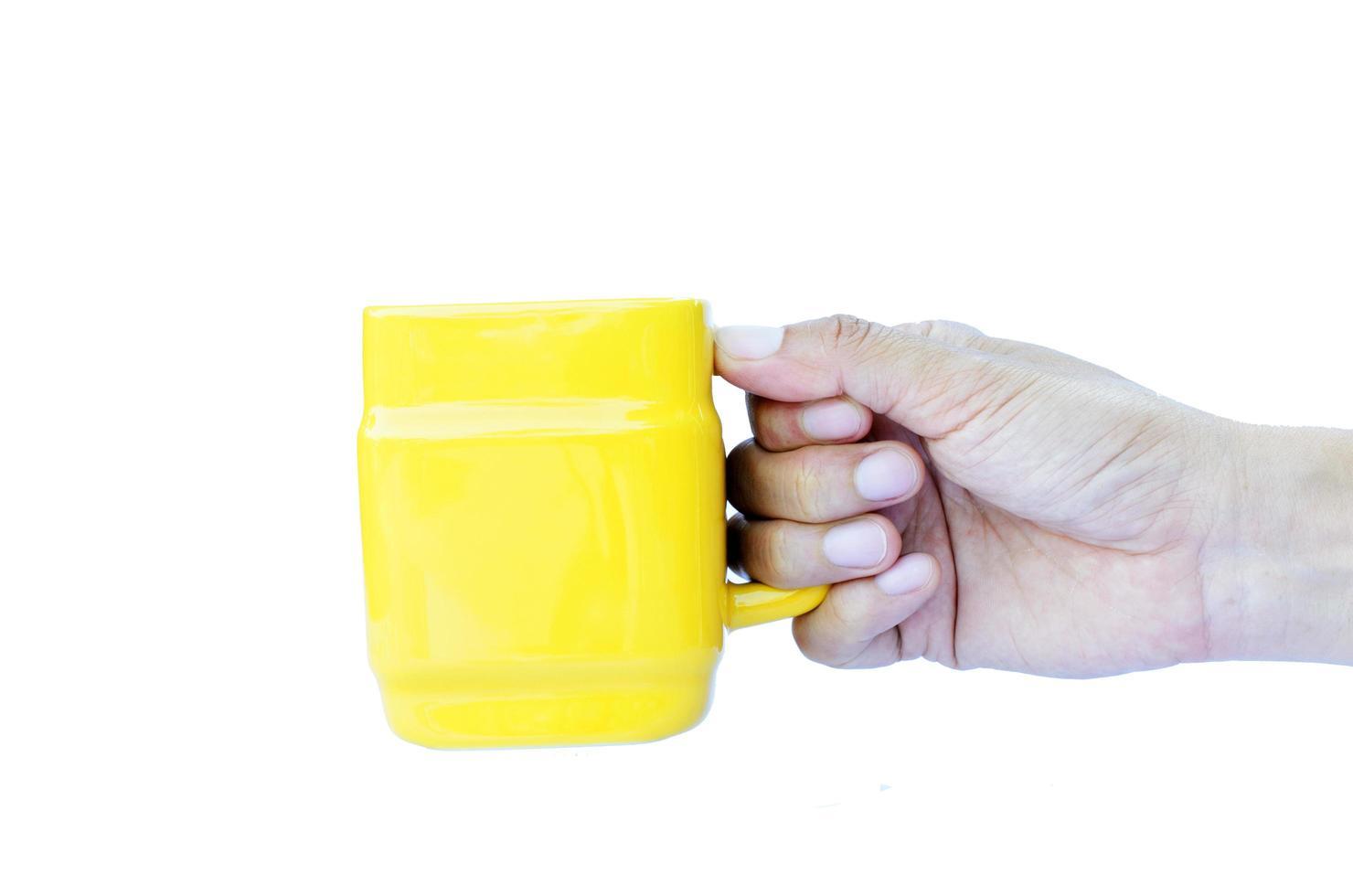 hand som håller gula koppar isolerade på vit bakgrund foto