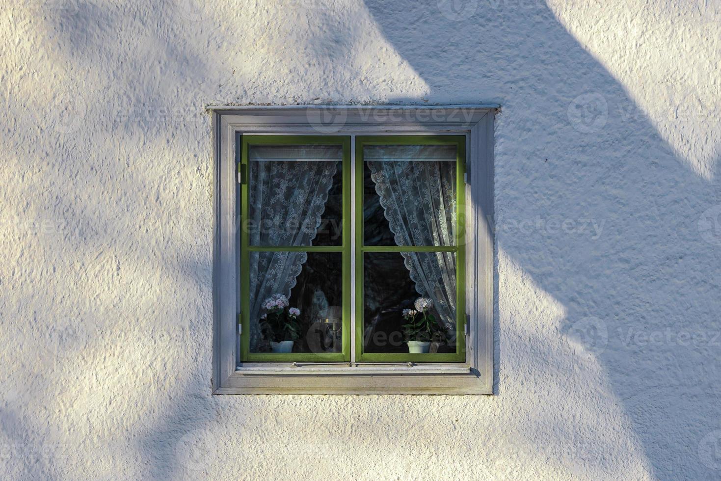 gammalt fönster med grön ram på en vit stenmur foto
