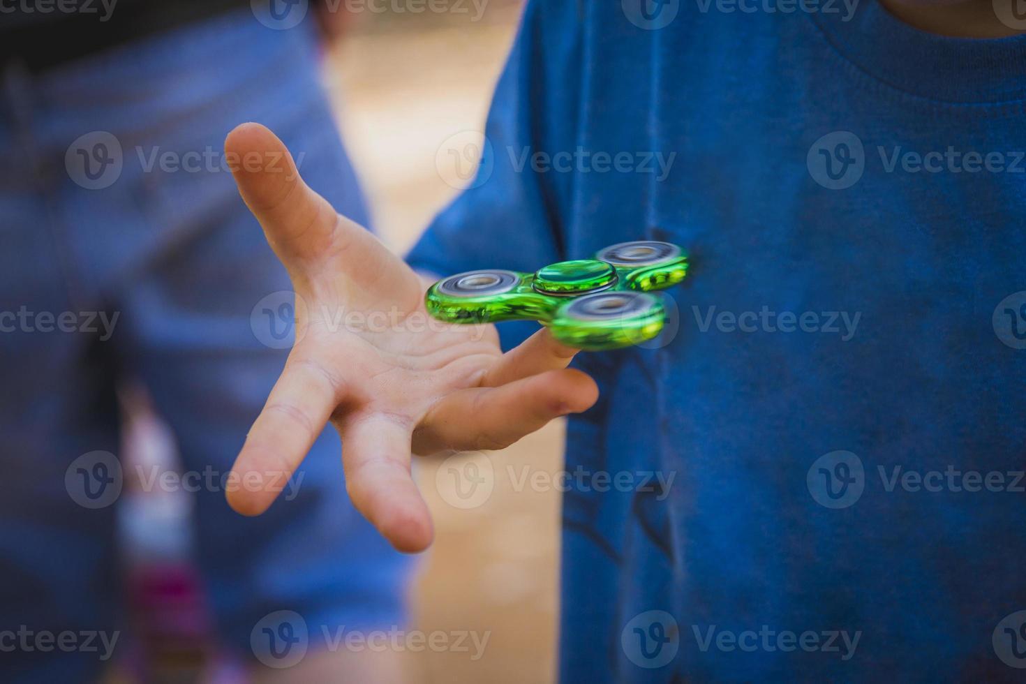 ung pojke leker med fidget spinner foto