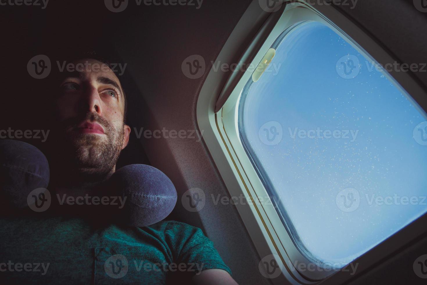 fundersam man med nackkudde vid fönstret på ett flygplan foto