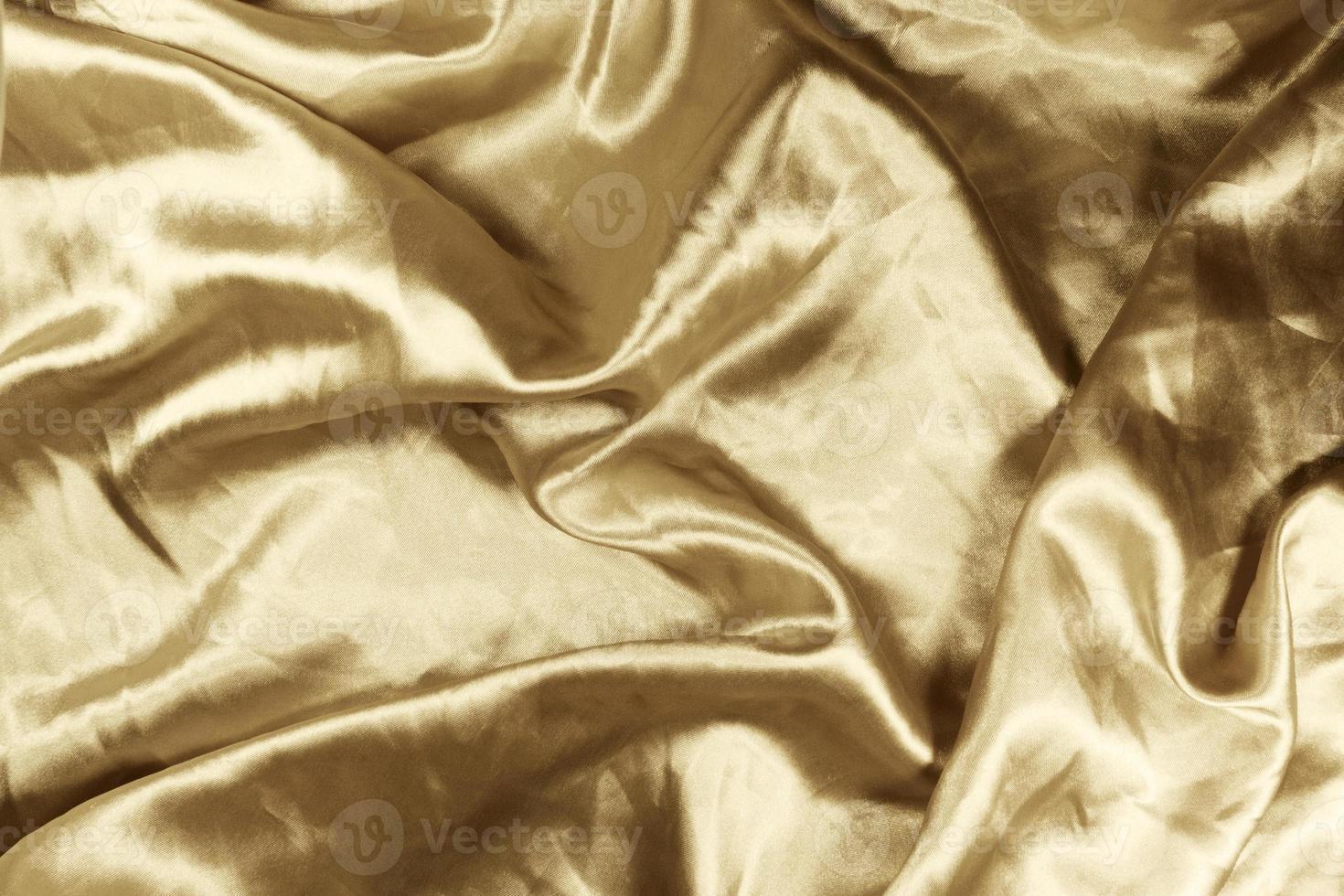 guld satin bakgrund med en abstrakt design som ger utseendet av glittrande vågor. foto