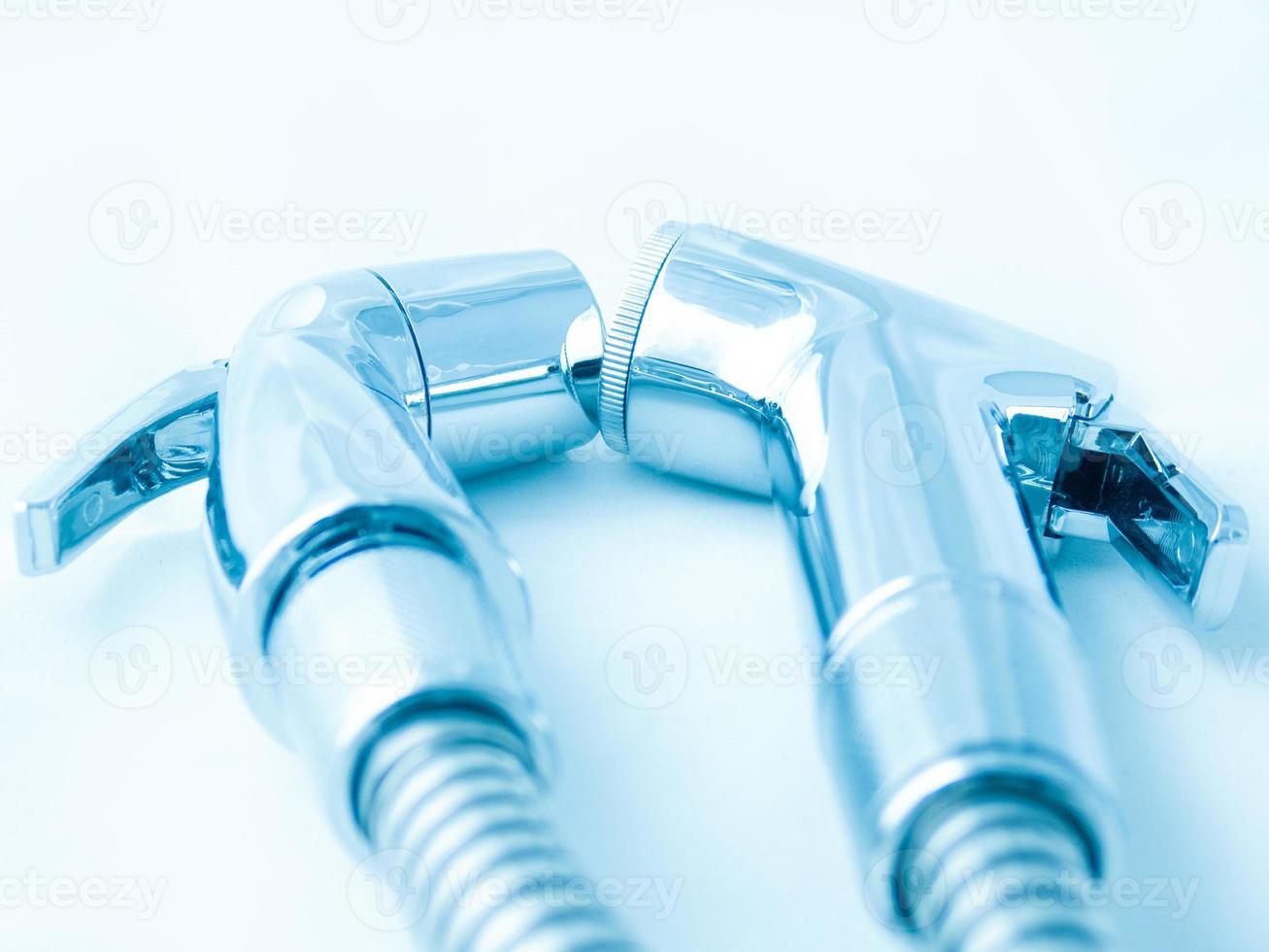 närbild av två bidéduschmaterial och spiralrör. designkonceptet är centrerat på en svaltonad spegelbakgrund som är mycket glänsande och dyr. rumpa rengöringsutrustning i badrummet foto