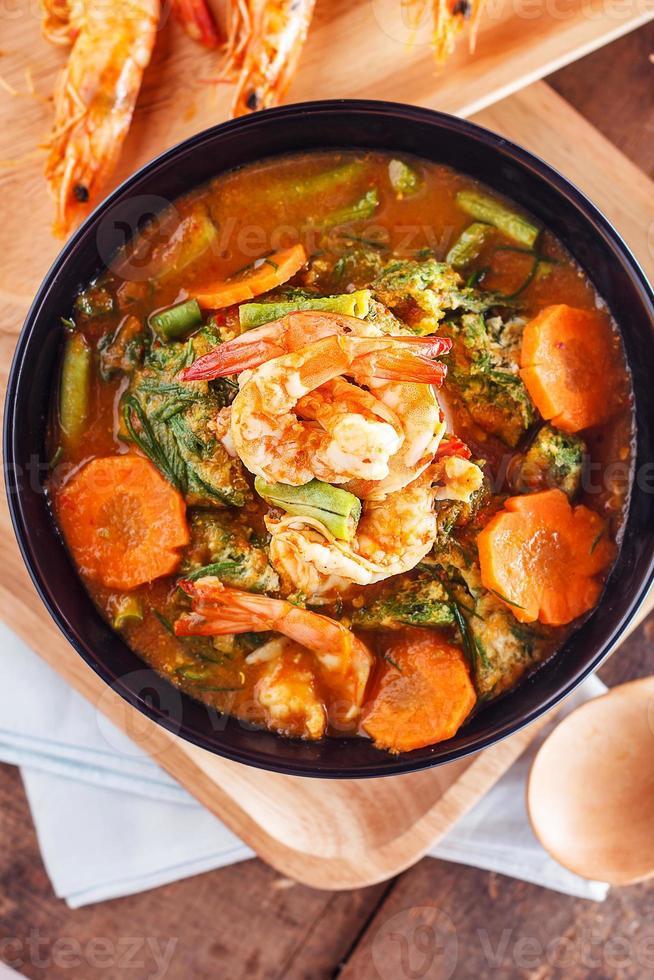 kryddig och soppa curry med räkor och grönsak omelett foto