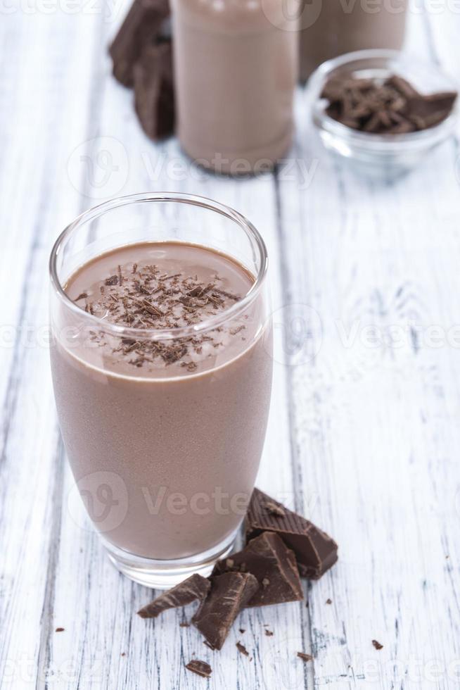chokladmjölk (på träbakgrund) foto