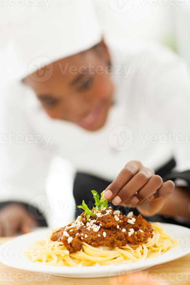 kvinnlig afrikansk kock som garnerar spaghetti foto