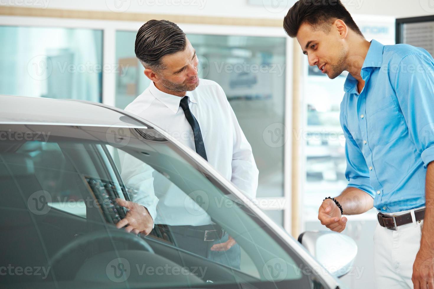 försäljningskonsult som visar ny bil till en potentiell köpare foto