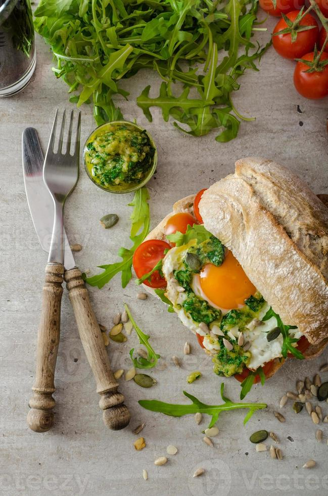 ciabatta med stekt ägg, tomater och pesto foto
