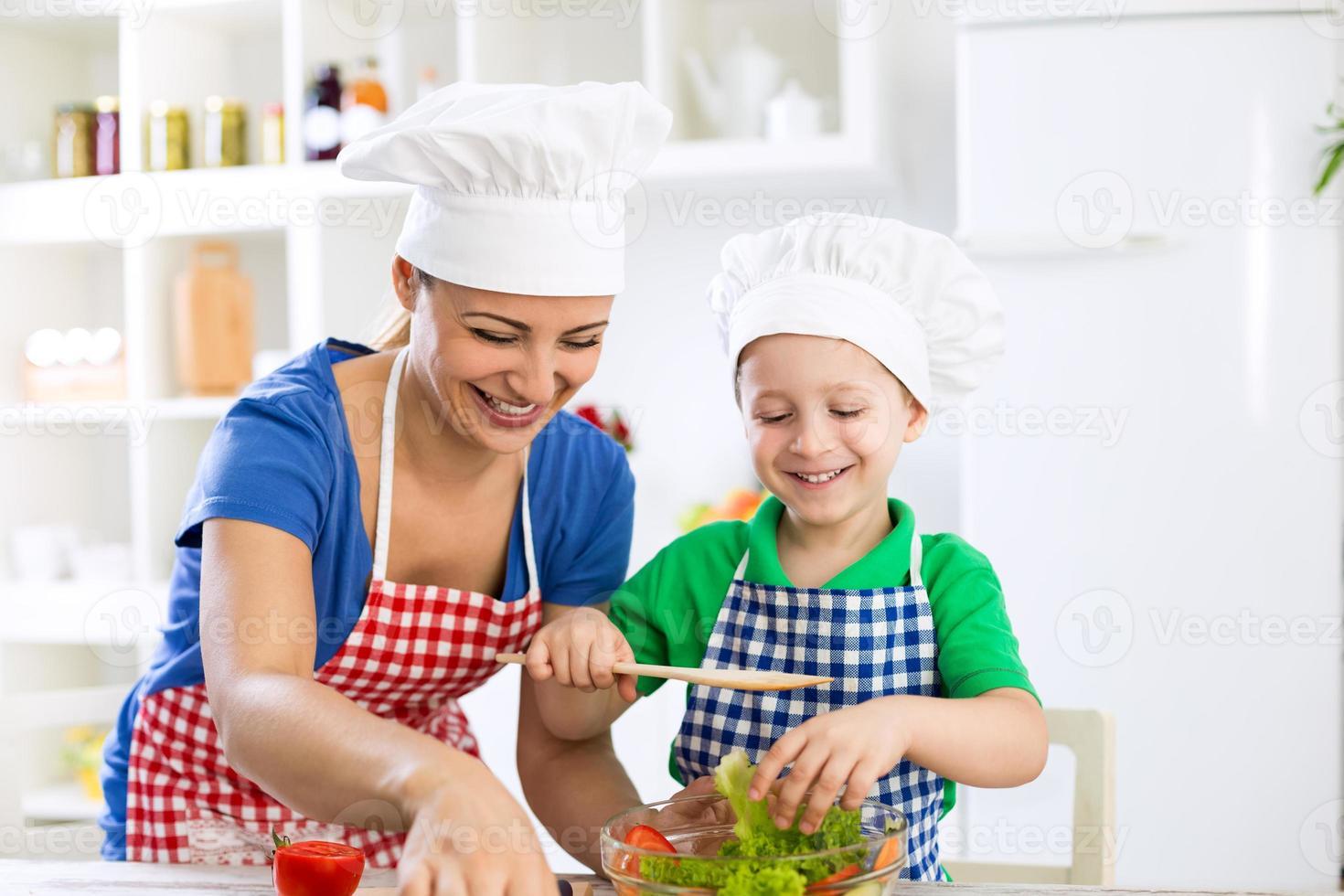 lycklig le familj som förbereder hälsosam mat foto