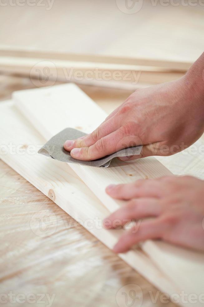 mans händer under renovering av golvet foto