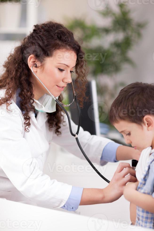 kvinnlig läkare undersöker pojken med stetoskop foto