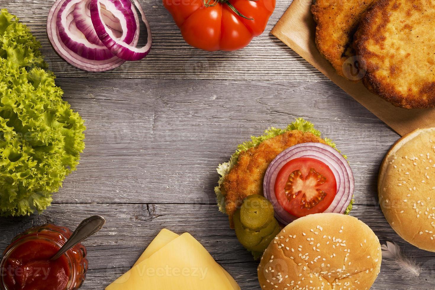 kycklingburgare med ost, sallad, tomat och lök foto