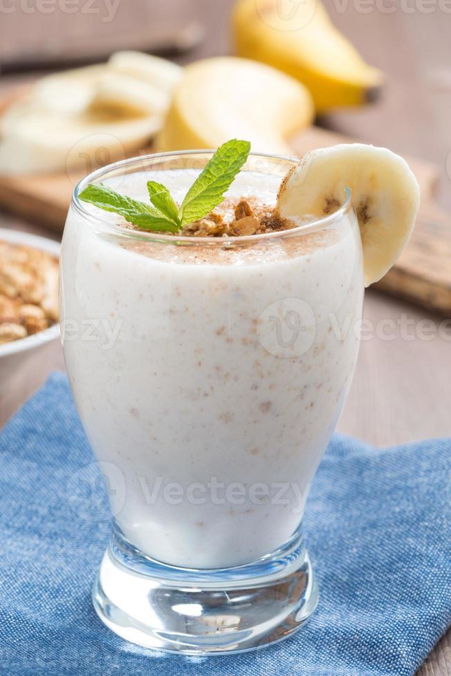 milkshake med banan, granola och kanel i ett glas, vertikalt foto
