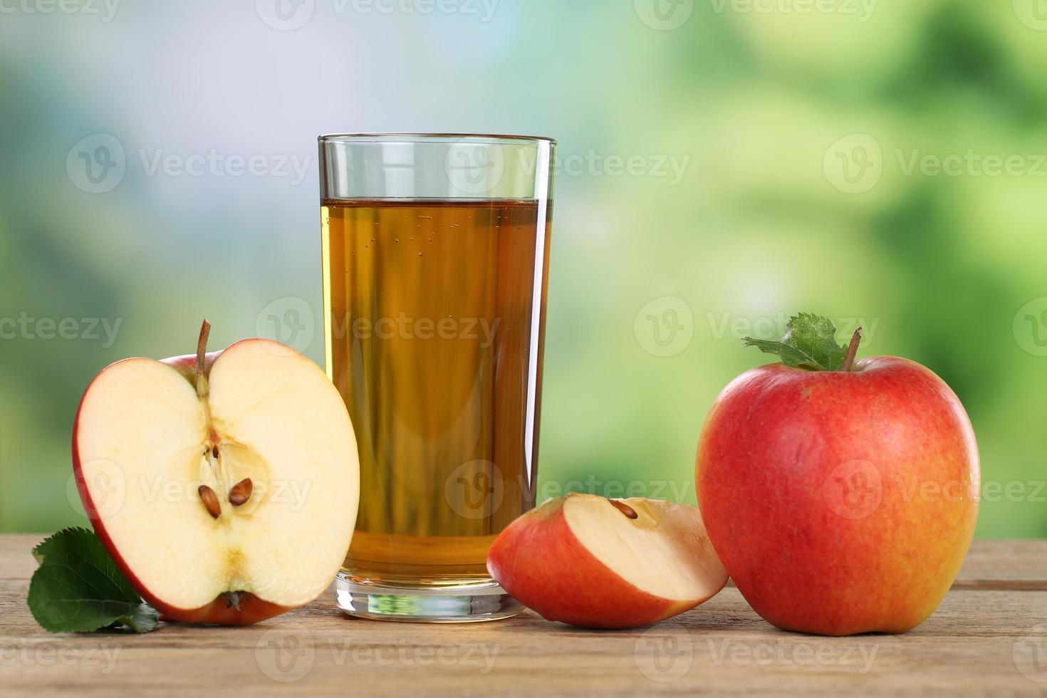 äppeljuice och röda äpplen på sommaren foto