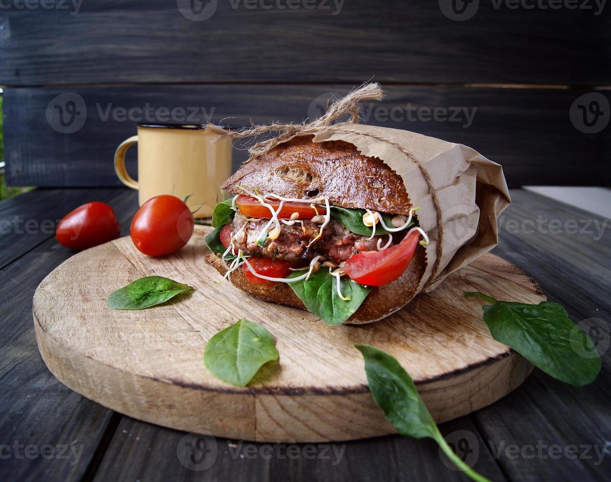 hamburgare med svart bröd och tomater på bordet foto