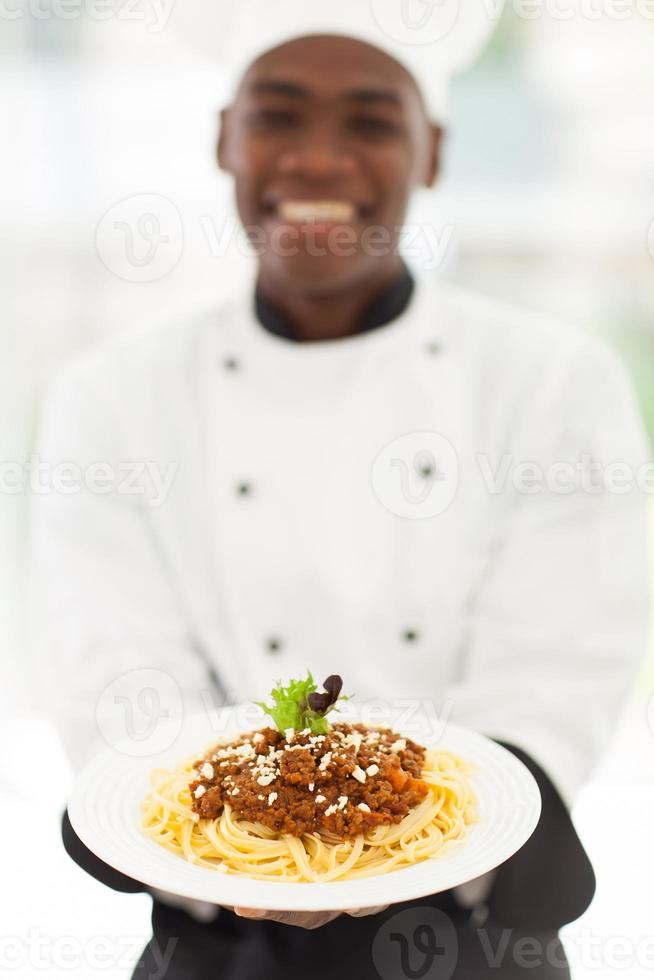 afrikansk manlig kock som presenterar spagetti foto
