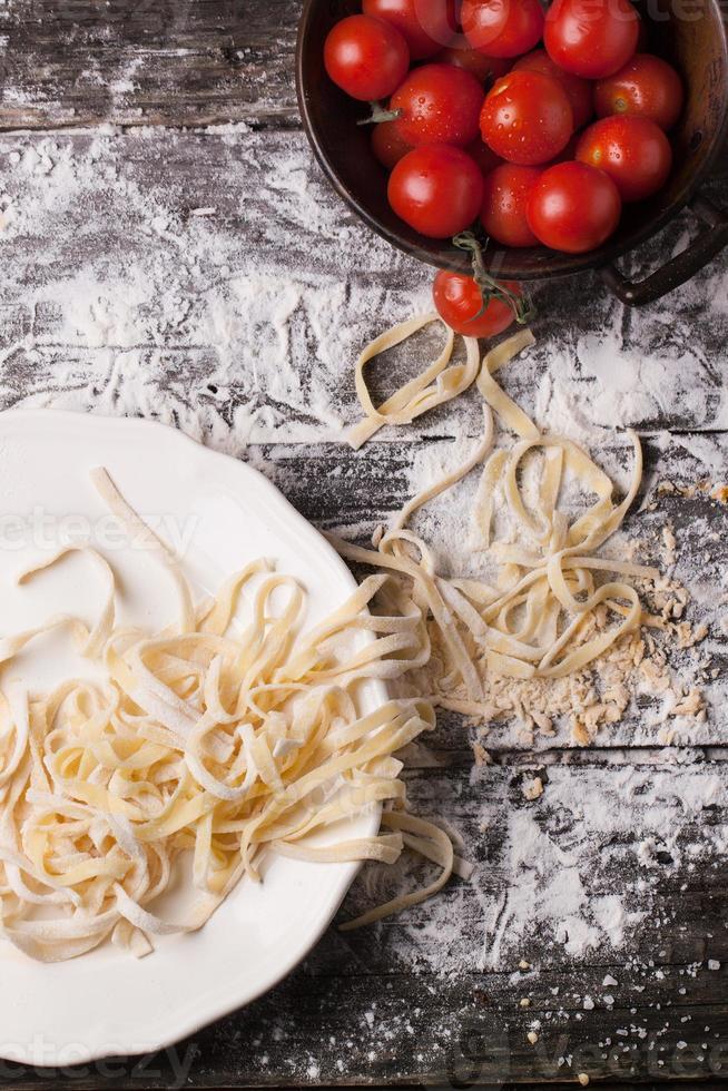 rå hemlagad pasta med tomater foto
