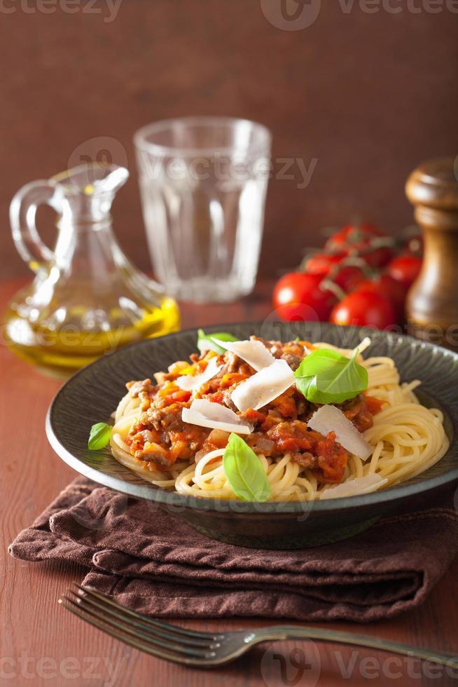 italiensk pastaspagetti bolognese med basilika på det rustika bordet foto