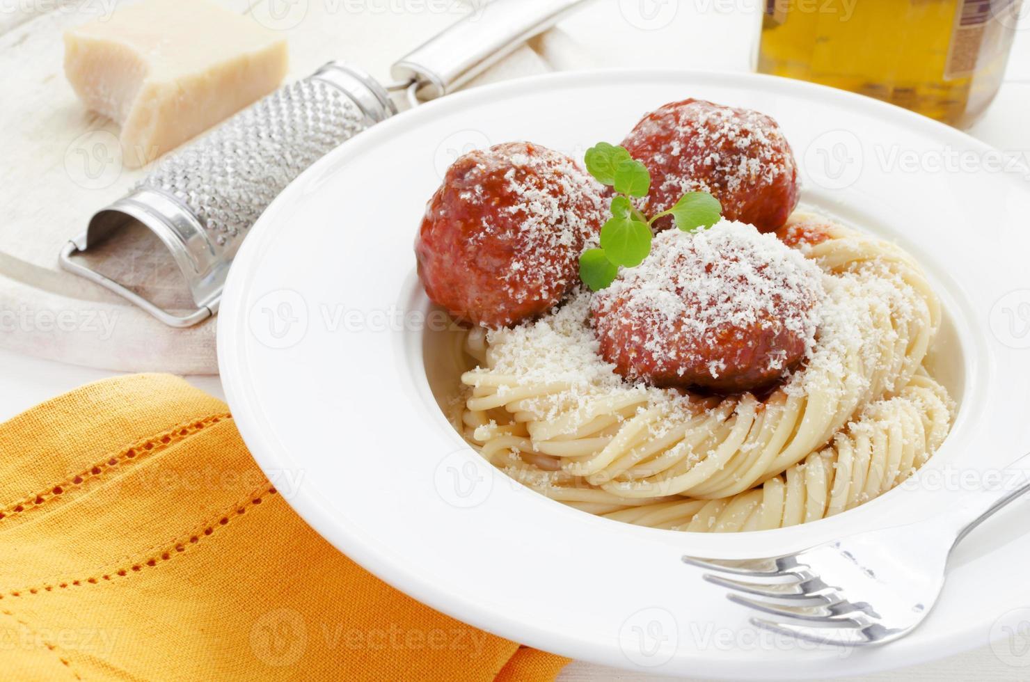 pasta med köttbullar i tomatsås, vattenkrasse och parmesanost foto