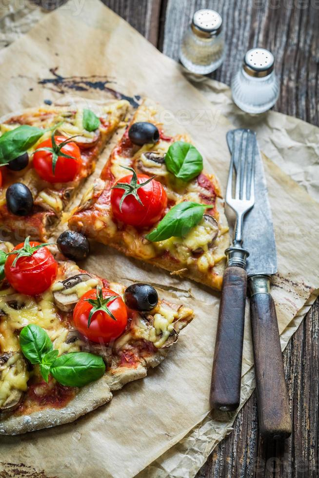 färsk pizza på papper och gamla träbord foto