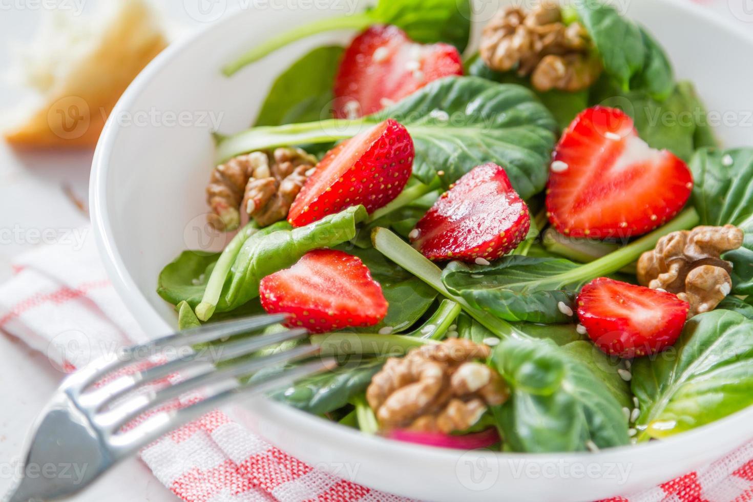 sallad med spenat, jordgubbe, nötter, olja, bröd, rutig servett foto