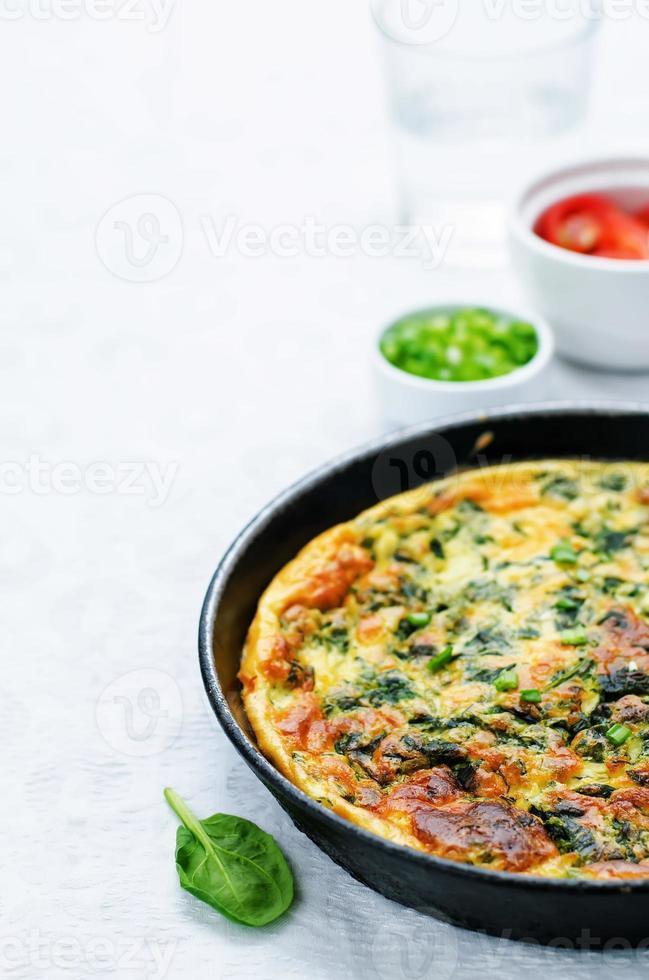 bakad omelett med spenat, dill, persilja och grön lök foto