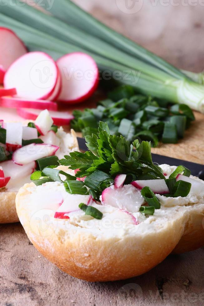 smörgåsar med färska grönsaker och gräddost på ett bord foto