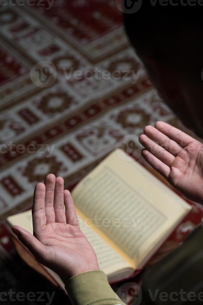 ung muslimsk kille som läser koranen foto