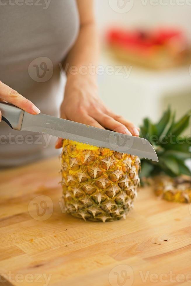 närbild på den unga kvinnan skära ananas foto