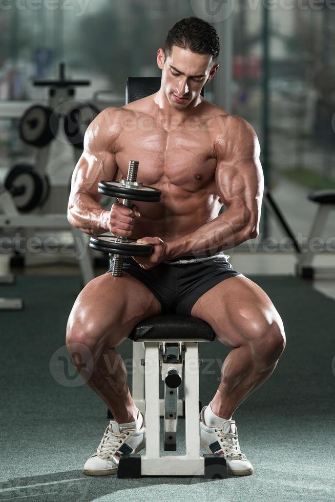 kroppsbyggare som utövar biceps med hantlar foto
