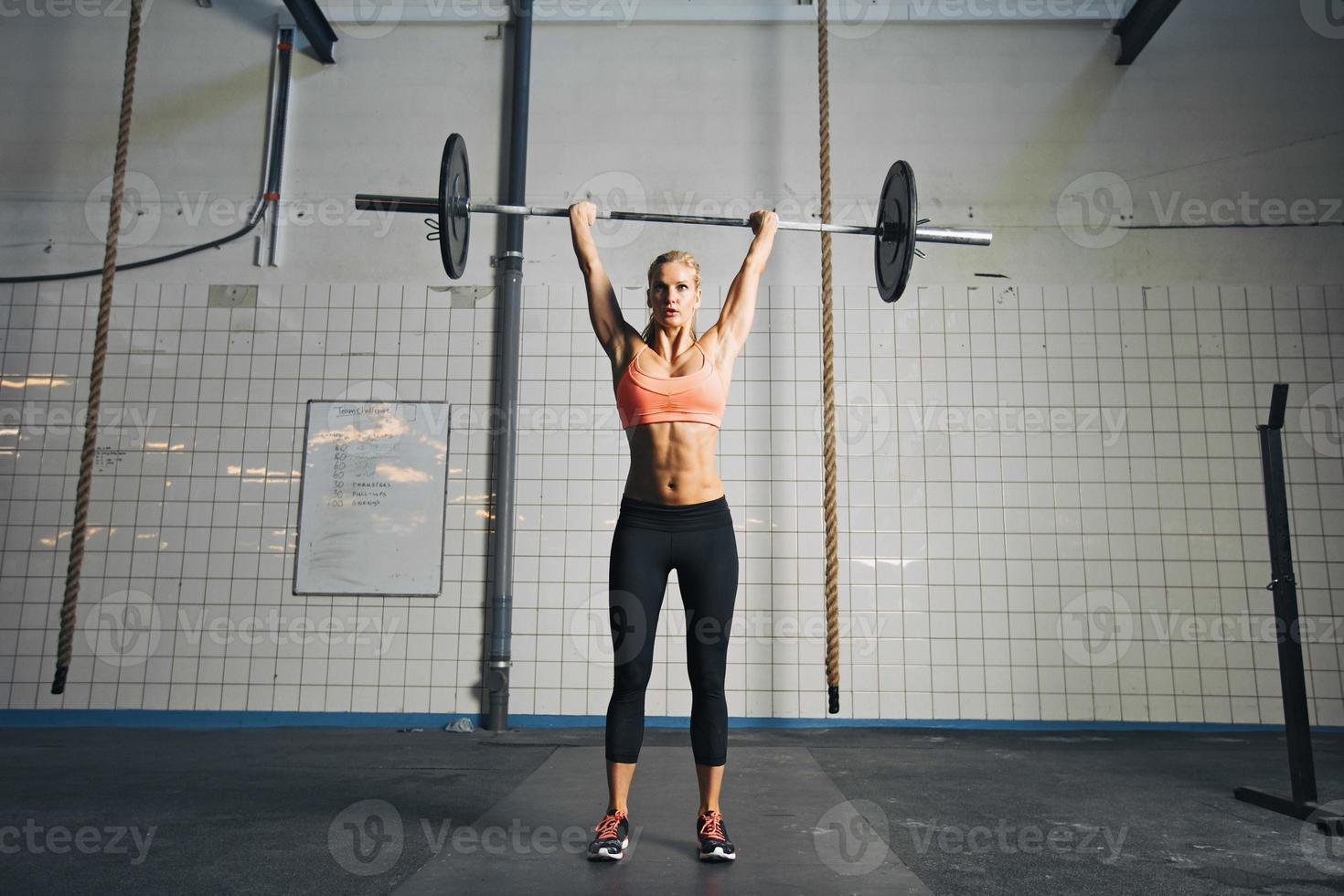 ung stark kvinna som gör viktlyft foto