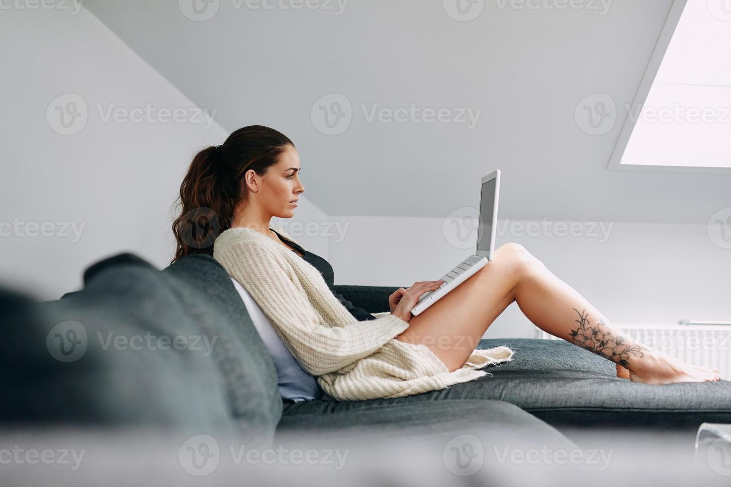 attraktiv brunett surfing internet på laptop foto