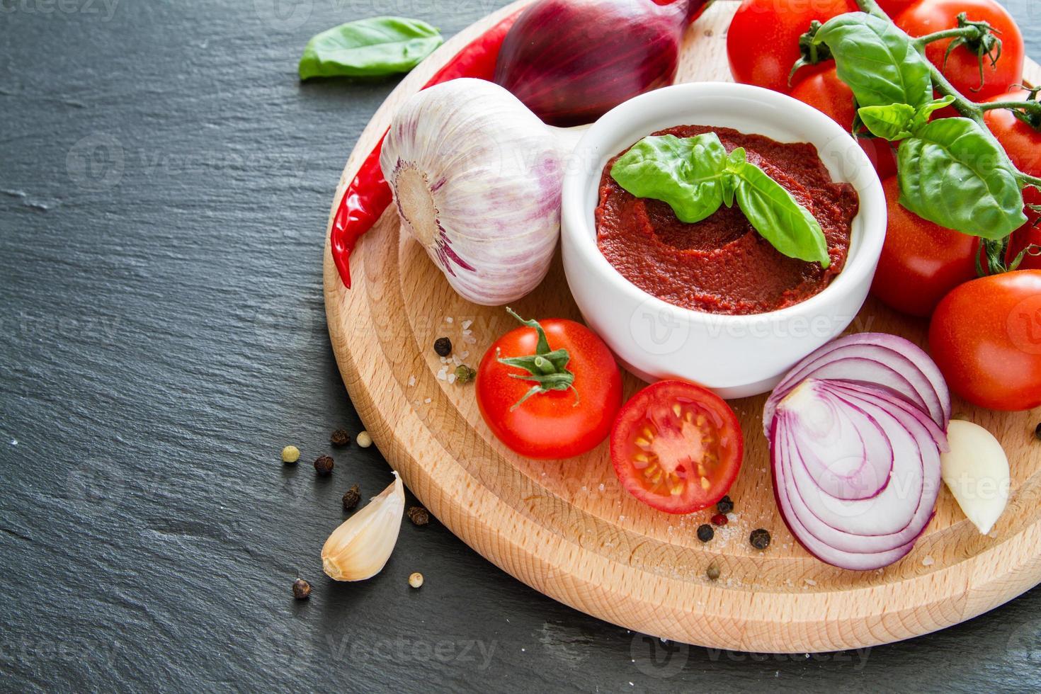 ingredienser för tomatsås - körsbärstomater, basilika, lök, vitlök, peppar foto