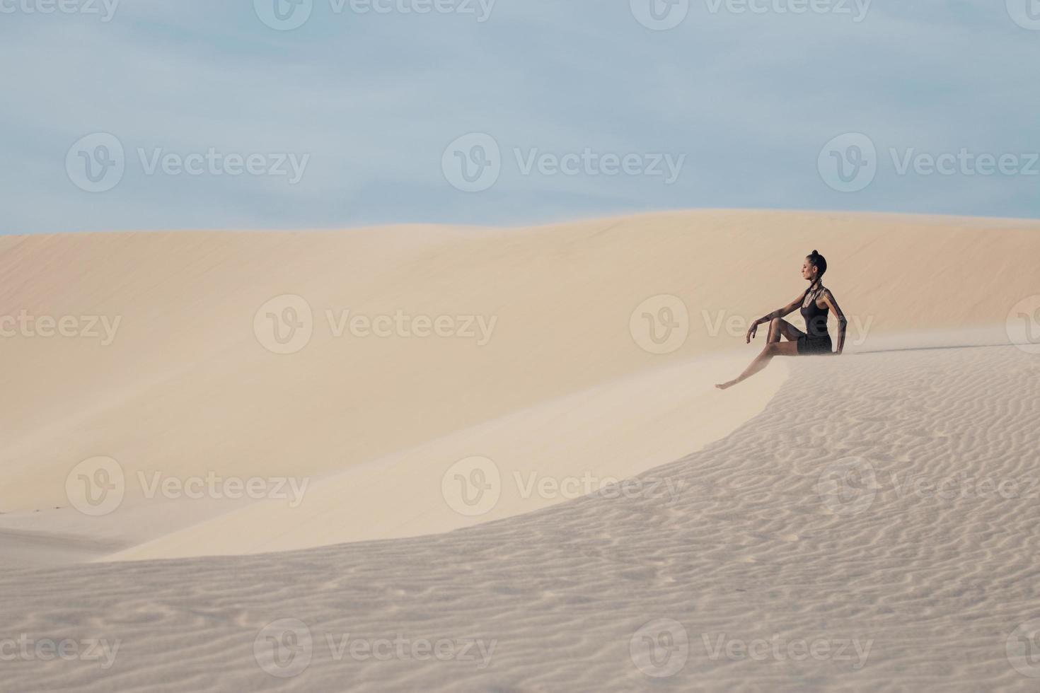 ung vacker kvinna i vita sanddyner som en goddes foto