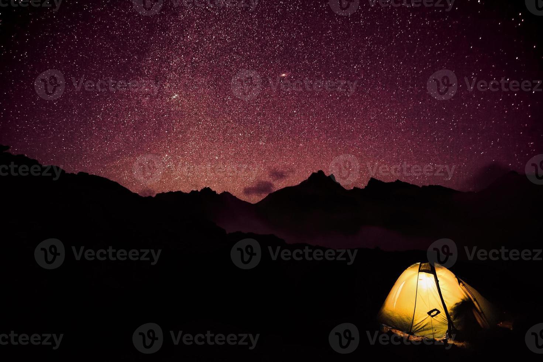 ljusa tält i berg och stjärnor foto