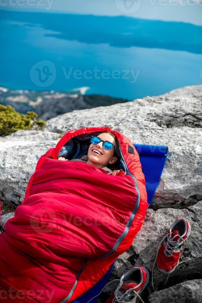 kvinna i sovsäck på berget foto