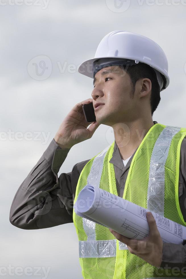 asiatisk industriell ingenjör på jobbet med telefon. foto