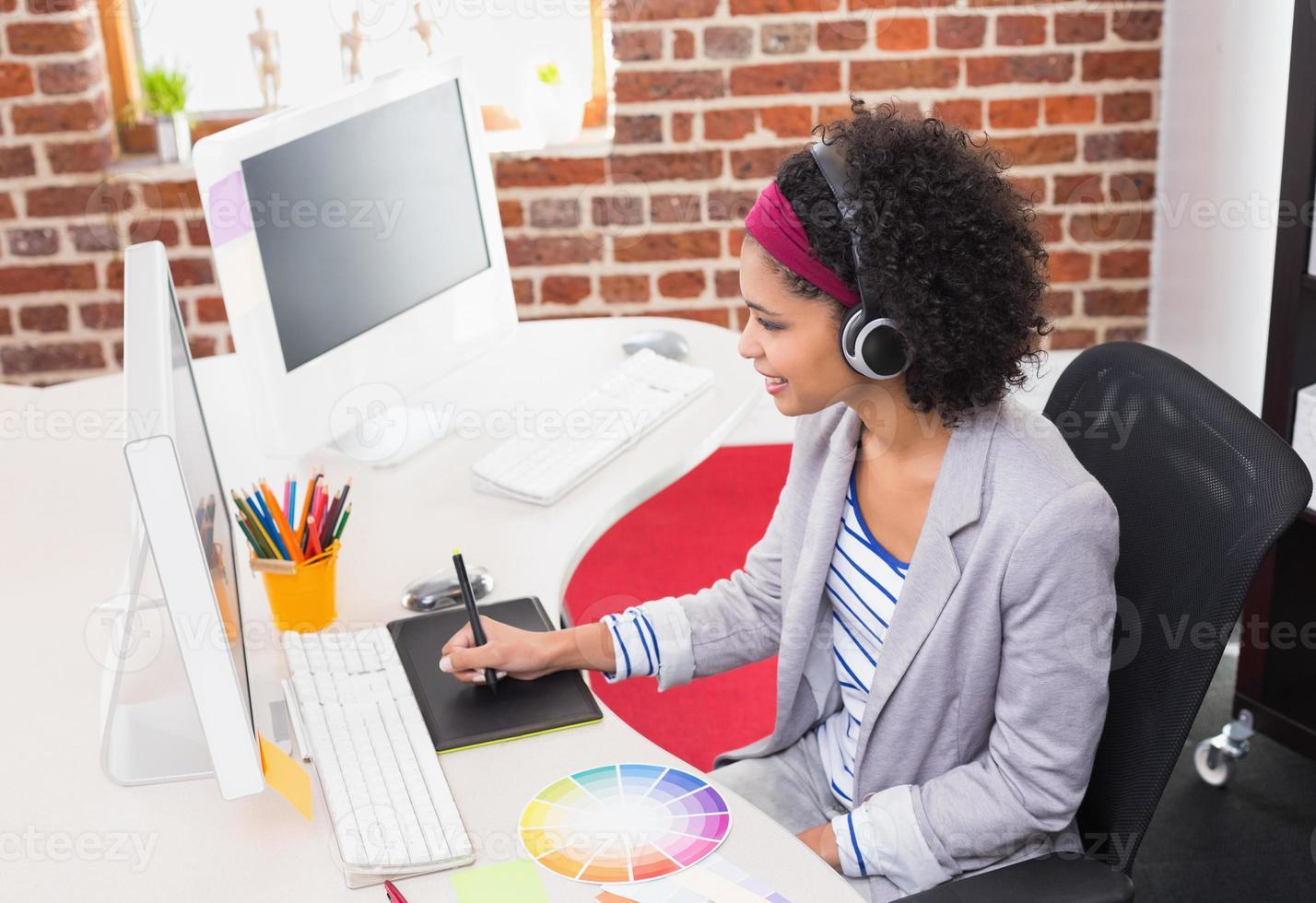 kvinnlig fotoredigerare som använder digitaliserare i office foto