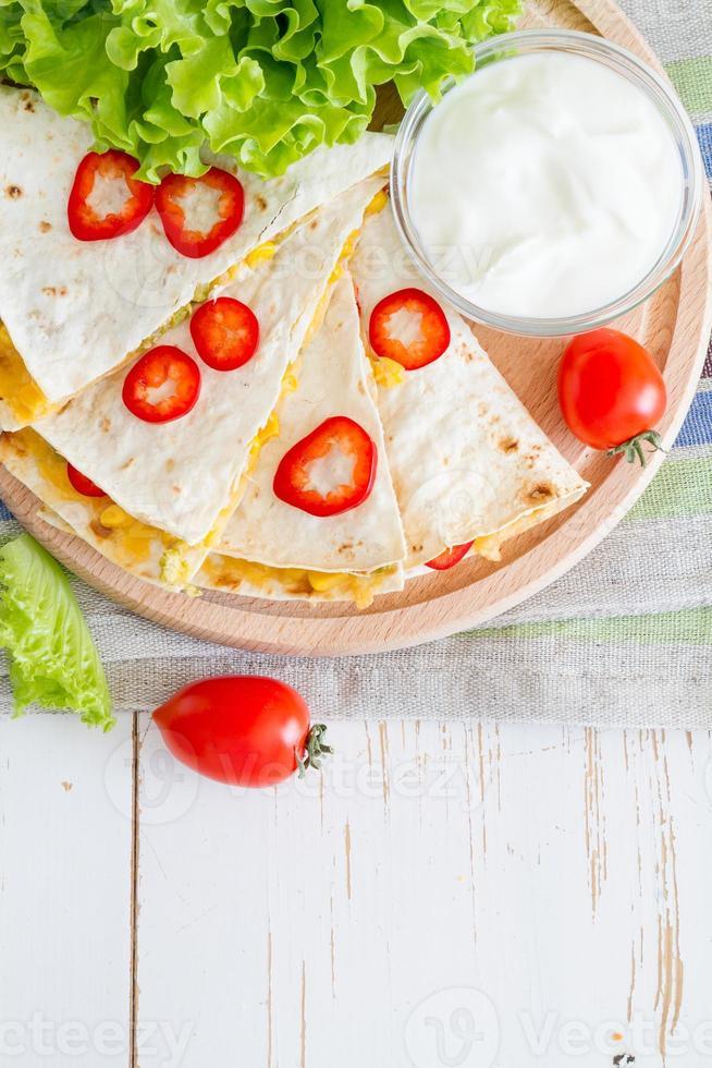 mexikanska quesadilla skivor serveras på träplatta med yoghurt sås foto