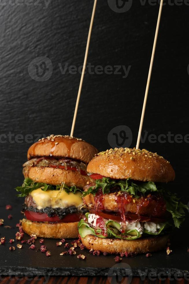 två stora dubbla hamburgare med färskt grillad nötkött isolerad på foto