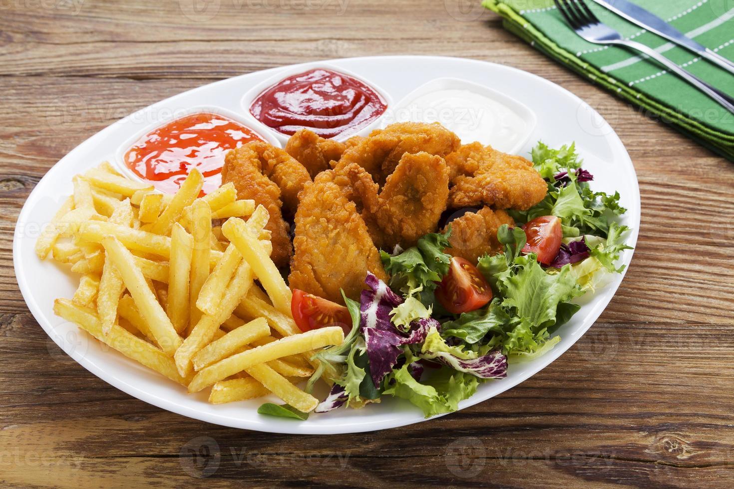 nuggets och chips serveras i en papperspåse med dopp foto