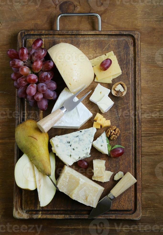 cheeseboard med blandade ostar (parmesan, brie, blå, cheddar) foto