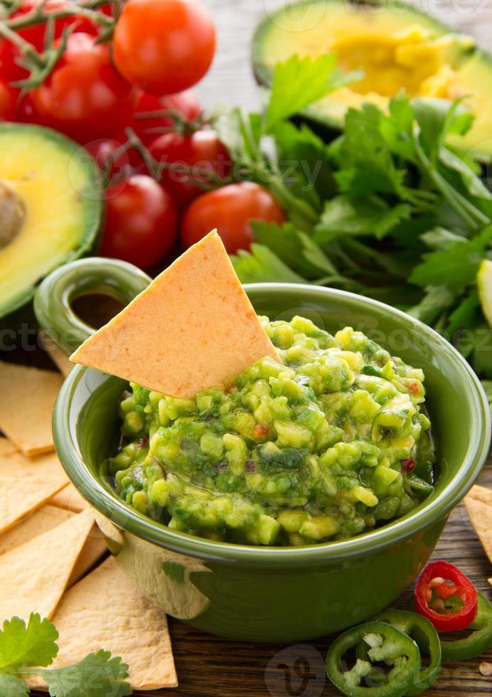 kopp med guacamole och majschips - traditionell mexikansk aptitretare foto