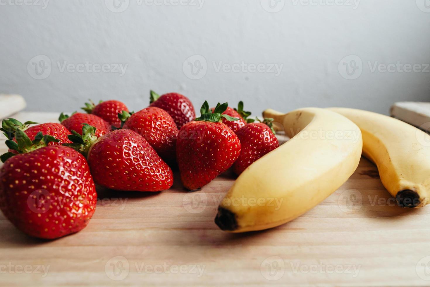 jordgubbar bananfrukter på träbord foto