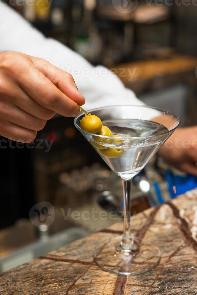 barman på jobbet, förbereder cocktails. förbereda martini med oliver. foto