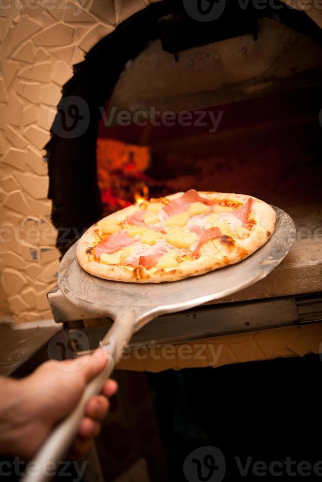 pizza som kommer ut ur en ugn foto