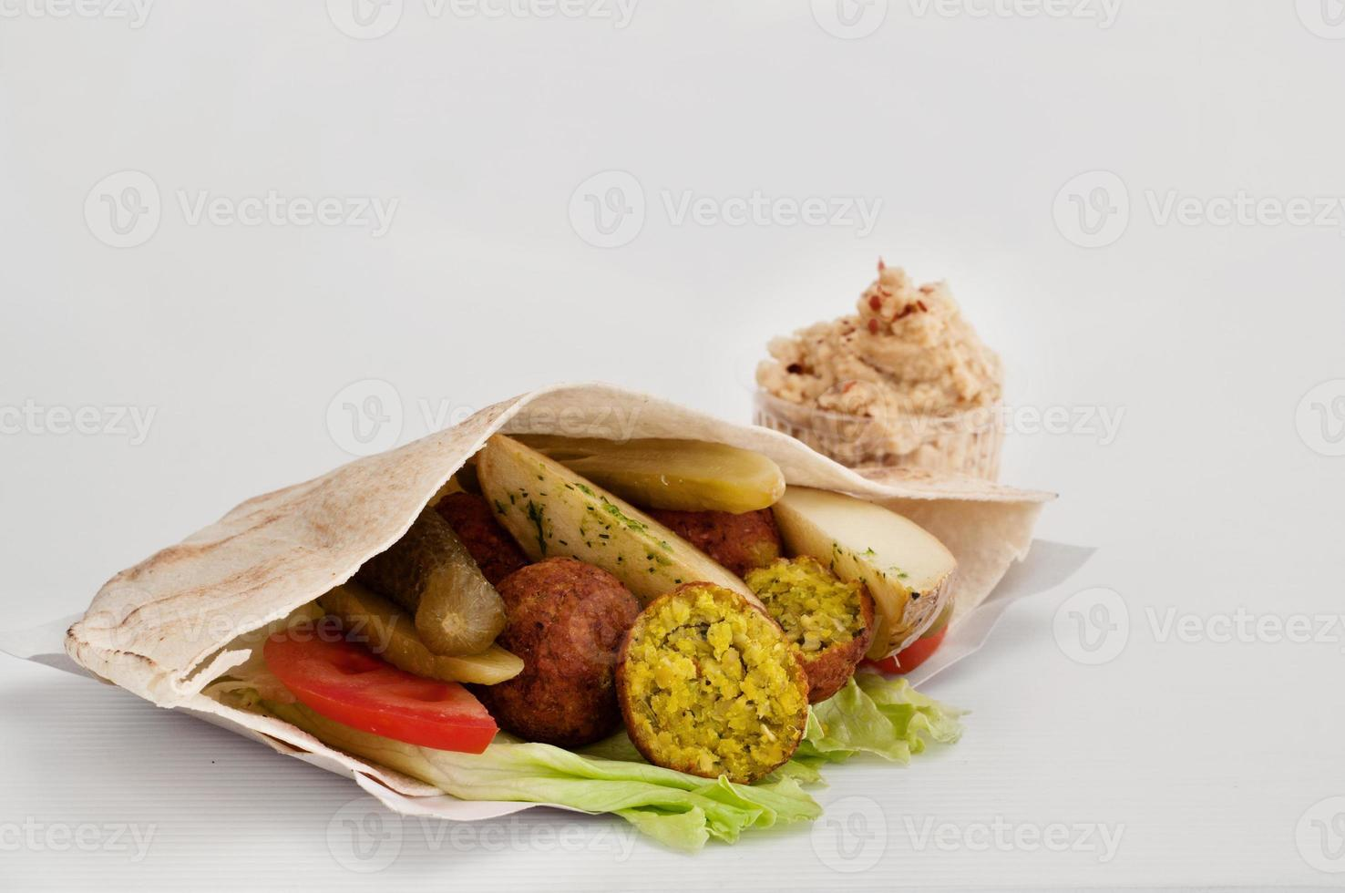 falafel med grönsaker i pitabröd och sås foto