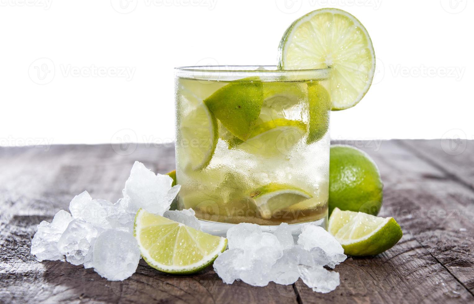 en caipirinha-cocktail garnerad med kalk på ett träbord foto