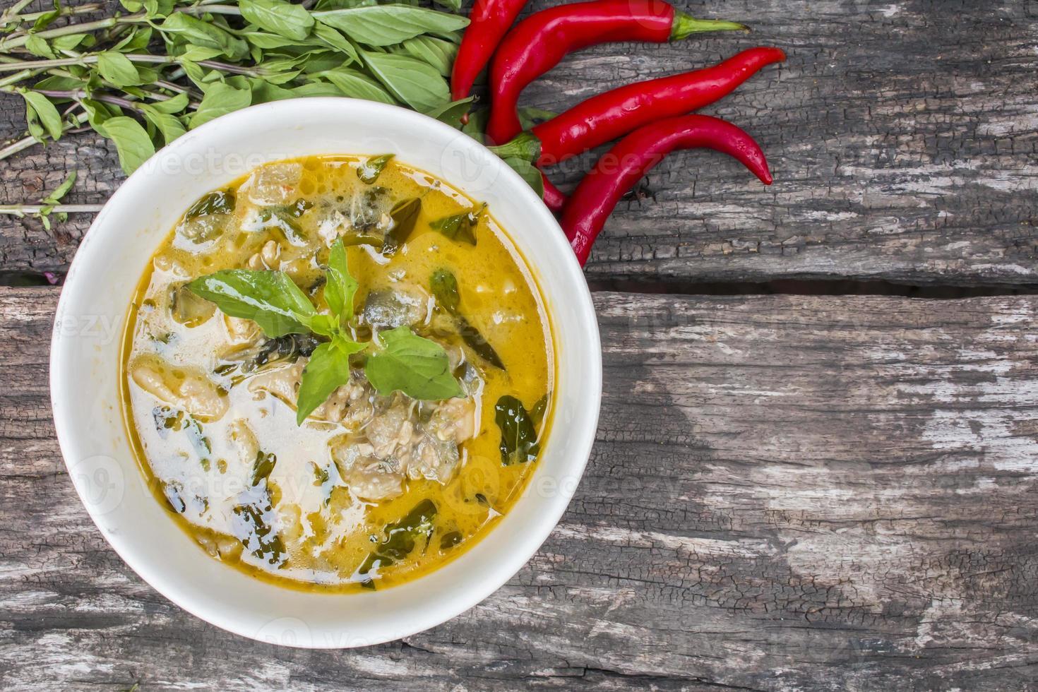 thailändsk kycklinggrön curry med gammal träbakgrund foto