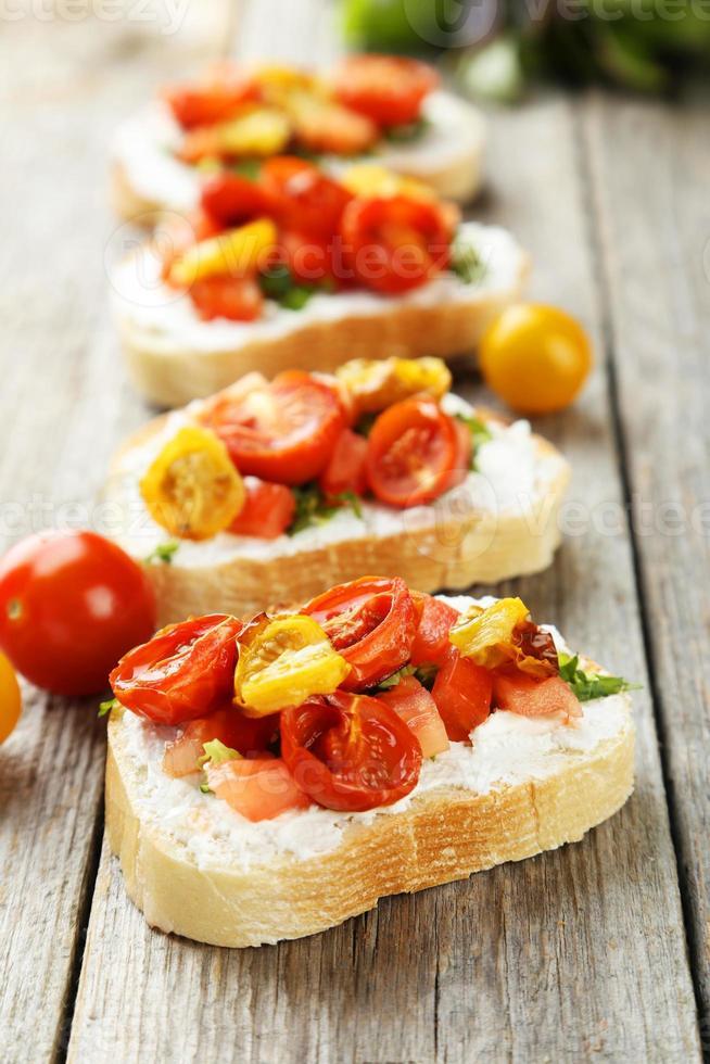 välsmakande färsk bruschetta med tomater på grå träbakgrund foto