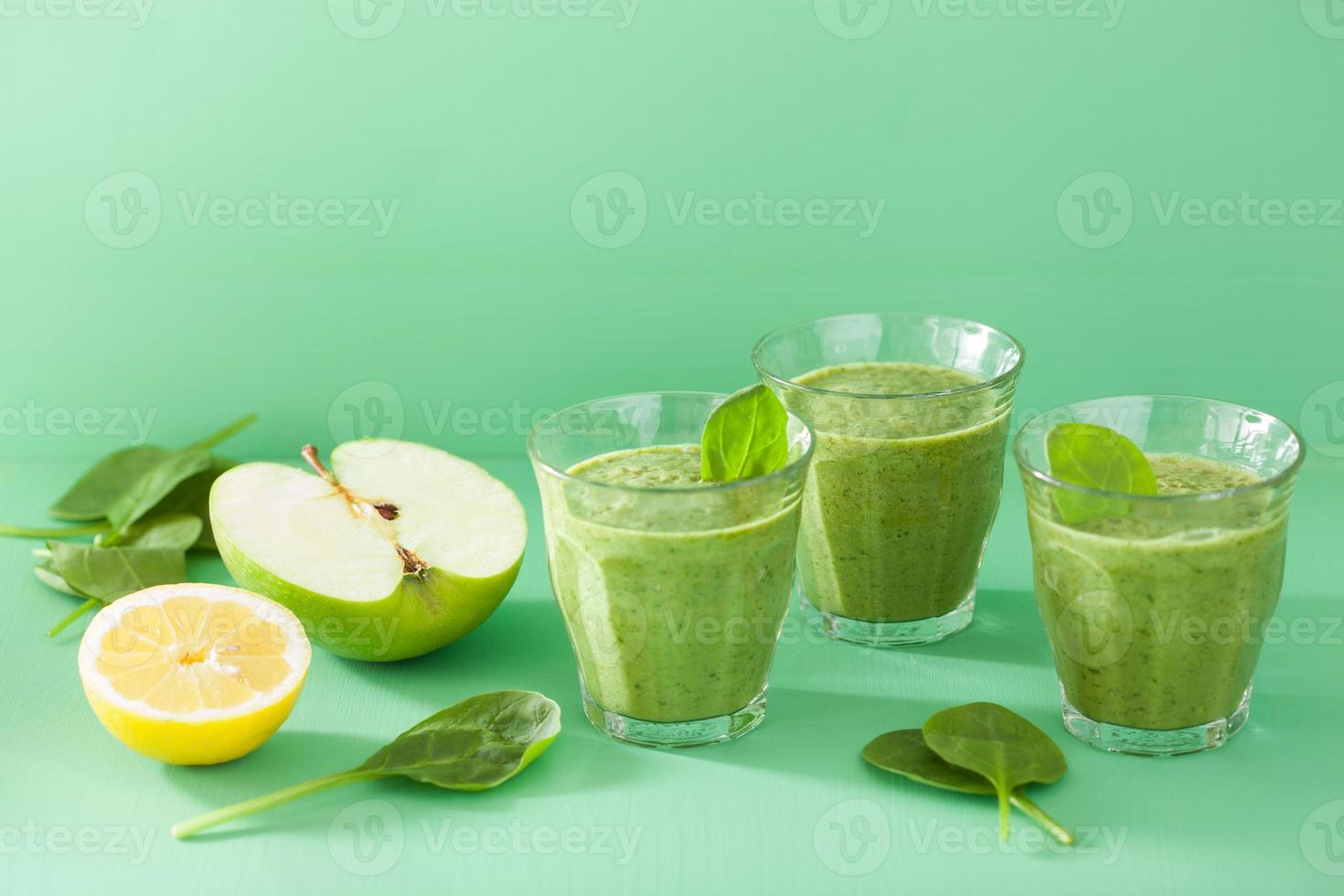 frisk grön smoothie med spenat lämnar äpple citron foto